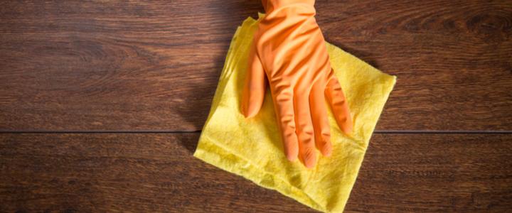 main gantée nettoyant une surface avec un chiffon microfibre